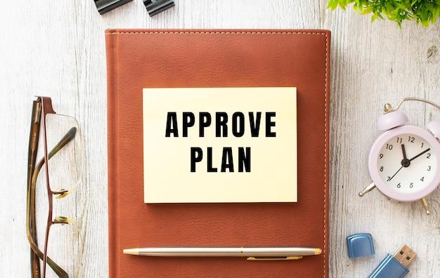 Notes z napisem approve plan na drewnianym stole. brązowy pamiętnik i długopis