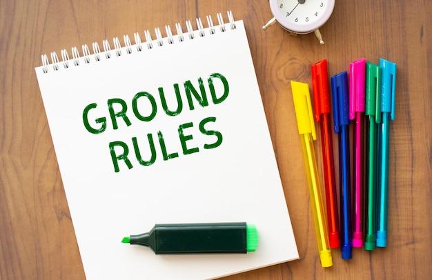 Notes z napisem ground rules na białej prześcieradle leży na brązowym drewnianym stole z kolorowymi długopisami.