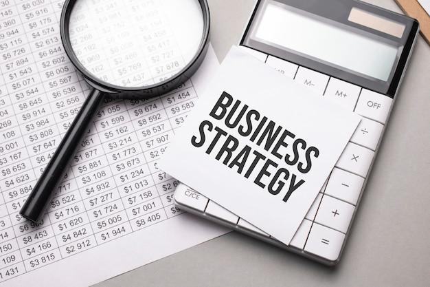 Notes z tekstem business strategy arkusz białego papieru na notatki, kalkulator, lupa