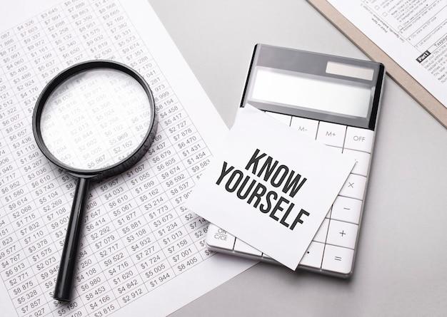 Notes z tekstem know yourself kartka białego papieru na notatki, kalkulator, lupa. pomysł na biznes.