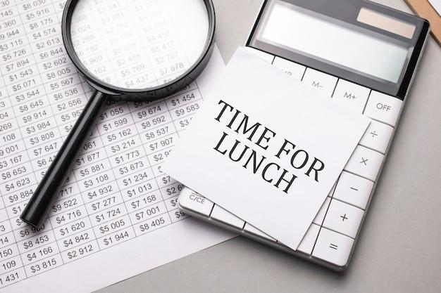 Notes z tekstem time for lunch arkusz białego papieru na notatki, kalkulator, lupa.