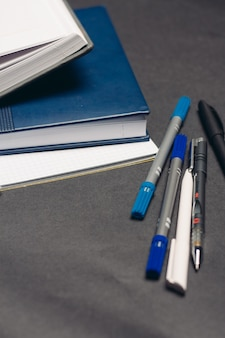 Notesy dokumenty książki długopisy pulpit szare tło biuro. wysokiej jakości zdjęcie