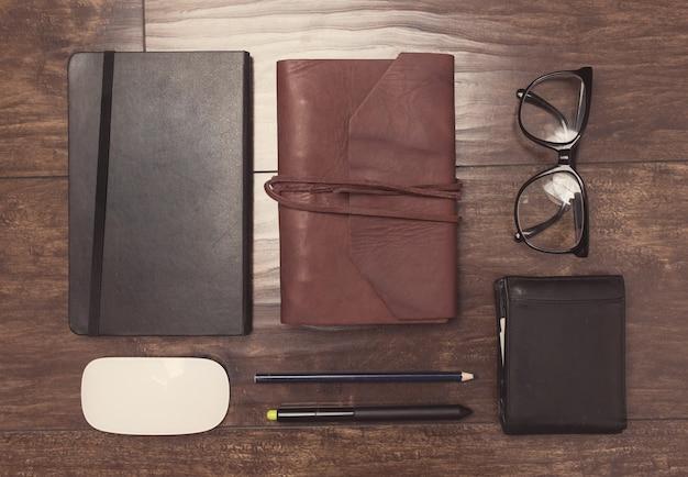 Notesy w skórzanej oprawie z ołówkami i okularami na drewnianym tle
