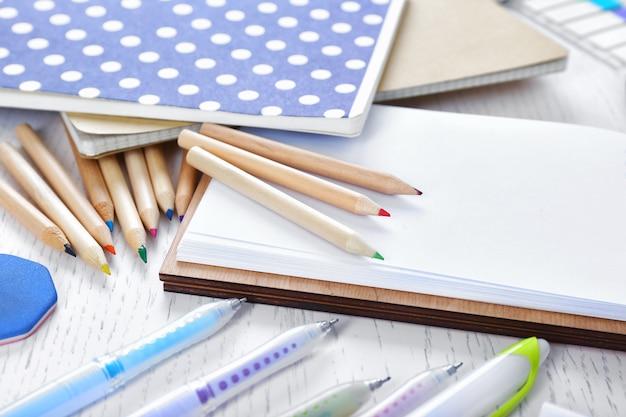Notesy z papeterią na białym stole