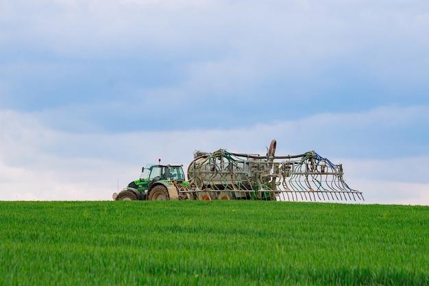 Nove hrady, czechy - 23 kwietnia 2019: opryskiwacz pracuje na zielonym polu. obróbka pszenicy herbicydem.