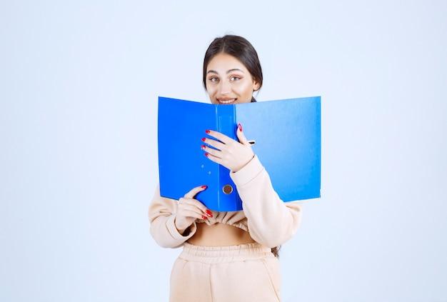 Nowa asystentka ukrywa twarz za niebieską teczką