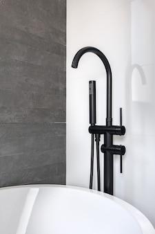 Nowa czarna bateria i natrysk na czystą, wyłożoną kafelkami biało-szarą ścianę łazienki w nowoczesnym mieszkaniu.