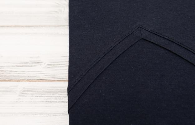 Nowa czarna v szyi koszula na białym drewnianym tle
