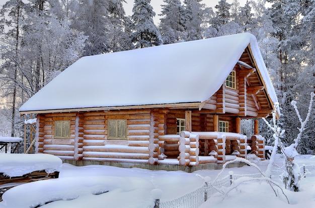 Nowa drewniana rosyjska łaźnia w słoneczny zimowy dzień, widok z zewnątrz, na tle zaśnieżonego lasu.
