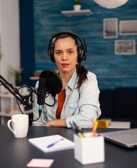 Nowa gwiazda mediów patrząca w kamerę podczas rozmowy do mikrofonu podczas podcastu wideo. influencer mediów społecznościowych nagrywający profesjonalne treści przy użyciu nowoczesnego sprzętu i cyfrowej stacji do strumieniowego przesyłania w internecie