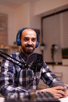 Nowa gwiazda mediów uśmiecha się ogłaszając zwycięzcę konkursu podczas swojego podcastu na żywo w domowym studiu przy użyciu profesjonalnego sprzętu. kreatywny program online produkcja na żywo gospodarz transmisji internetowej przesyłający treści na żywo