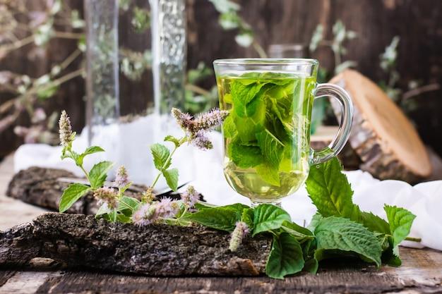 Nowa herbata w szkle, trawa na drewnianym stole
