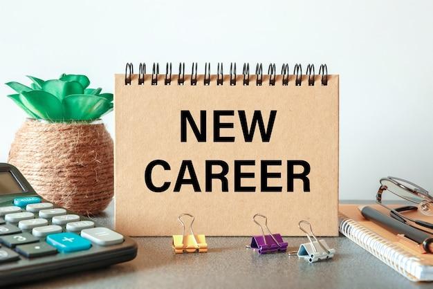 Nowa kariera jest zapisana w zeszycie na biurkowym stole z artykułami biurowymi.