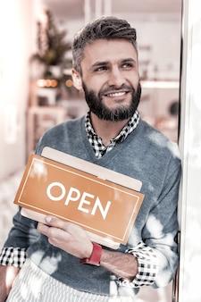 Nowa kawiarnia. zachwycony przystojny mężczyzna stojący ze znakiem podczas otwierania swojej kawiarni