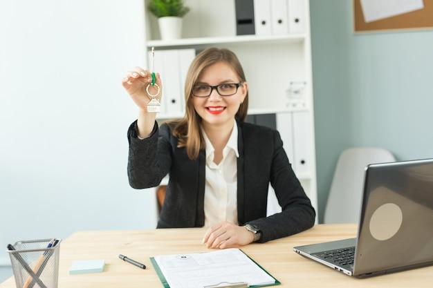 Nowa koncepcja domu i nieruchomości - szczęśliwa kobieta pośrednika w handlu nieruchomościami, dając klucze i pokazując kciuk do góry.