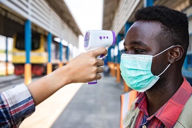 Nowa koncepcja normalna i ukryta. pracownik za pomocą medycznego cyfrowego termometru na podczerwień mierzy temperaturę człowiekowi w warsztacie kolejowym