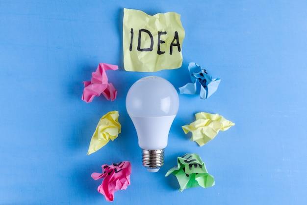 Nowa koncepcja pomysłu, zmięte kulki papieru i żarówka