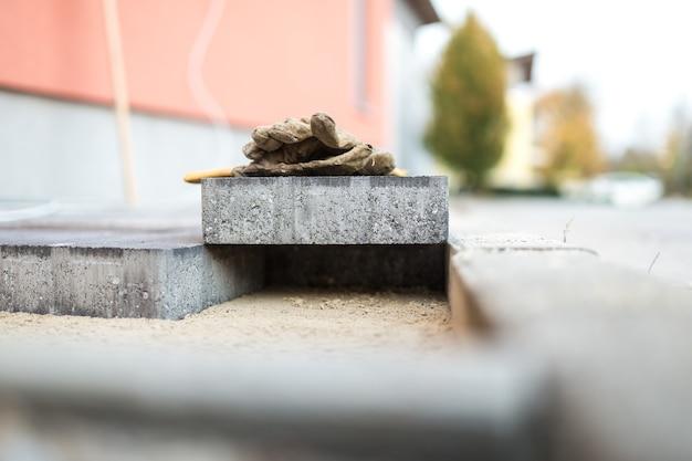 Nowa kostka brukowa spoczywa nad nowo zainstalowanymi cegłami na zewnątrz w środowisku miejskim, balansując w poprzek szczeliny, która jest zbyt ciasna, z rękawicami roboczymi na górze.