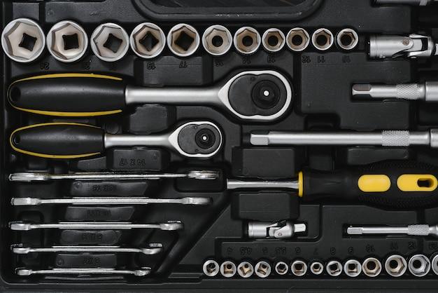 Nowa kwadratowa czarna skrzynka narzędziowa na tle drewniane tekstury. widok z góry