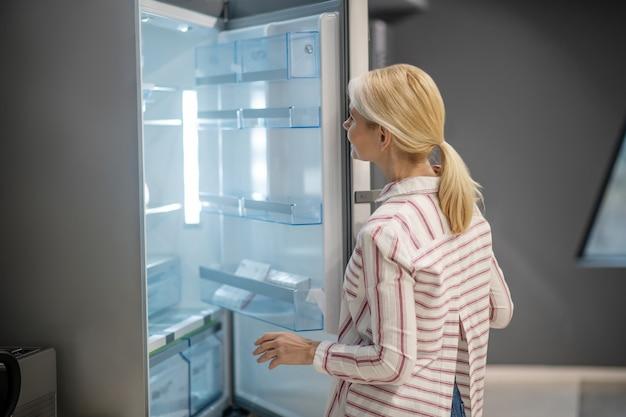 Nowa lodówka. blondynka klientka wybiera lodówkę w megastore