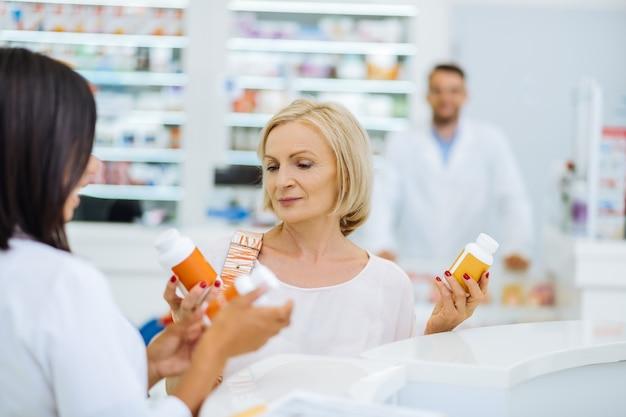 Nowa medycyna. sylwetka brunetki chemika, która stoi w swoim miejscu pracy i czeka na klientów