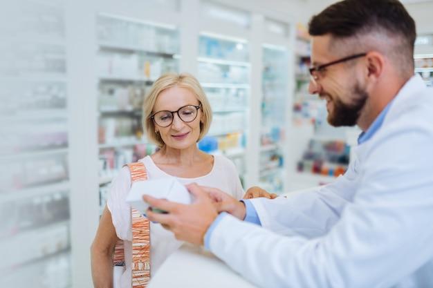 Nowa medycyna. zdjęcie profilowe młodego chemika, który zachowuje uśmiech na twarzy podczas demonstrowania pakietu