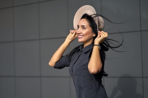 Nowa młodzieżowa kolekcja odzieży damskiej. plenerowego zbliżenie portreta atrakcyjna śmieszna dziewczyna z długie włosy jest ubranym młodą szarą obszerną suknią i eleganckim kapeluszem w wietrznym dniu.