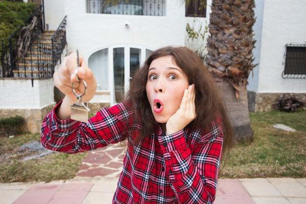 Nowa nieruchomość domu i najemca domu młoda kobieta śmieszne trzymając klucz przed swoim nowym domem