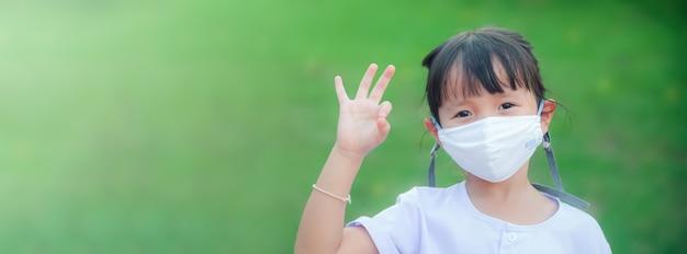 Nowa norma: mała dziewczynka ubrana w maskę z tkaniny w celu ochrony przed chorobami lub zanieczyszczeniem powietrza, podnosi rękę w prawidłowej pozycji