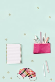 Nowa normalna koncepcja szkoły biurkowej z artykułami biurowymi dla dziewczynki i środkami ochrony osobistej.