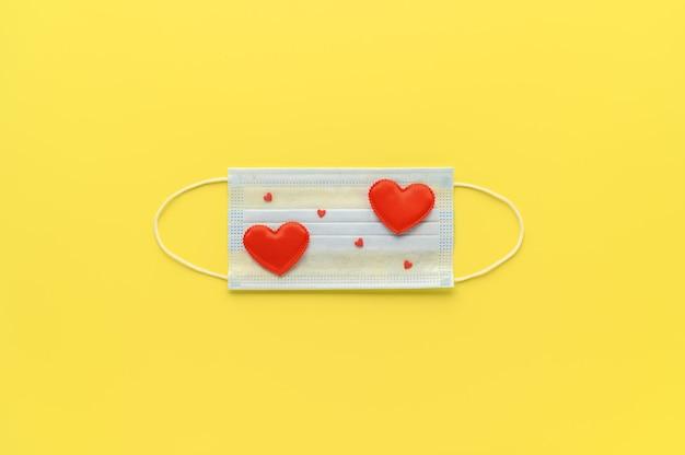 Nowa normalna koncepcja walentynek. medyczna maska na twarz ozdobiona czerwonymi sercami na świecącym żółtym tle. widok z góry, miejsce na kopię