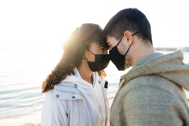 Nowa normalna para zakochanych w związku z dystansem społecznym: mężczyzna i dziewczyna patrzą sobie w oczy twarzą w twarz z odbiciem zachodzącego słońca