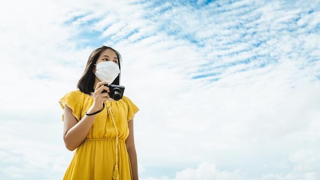 Nowa normalna podróżniczka azjatycka kobieta z maską i aparatem w niebo baclground tajlandia