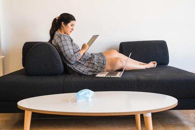 Nowa normalna sytuacja, dziewczyna w sukience odpoczywa na kanapie podczas pracy zdalnej z laptopem i tabletem.