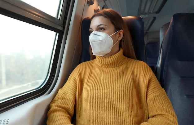 Nowa normalność. pasażer w masce ochronnej stojący w pociągu z zachowaniem zasad bhp.