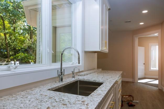 Nowa nowoczesna biała kuchnia z wbudowanym chromowanym kranem