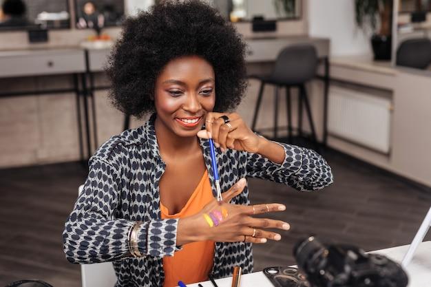 Nowa paleta. piękna ciemnoskóra kobieta nosząca złotą bransoletkę demonstrująca publiczności nowe próbki