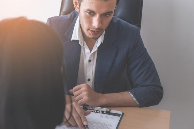 Nowa pracownica podpisuje umowę o pracę po rozmowie kwalifikacyjnej