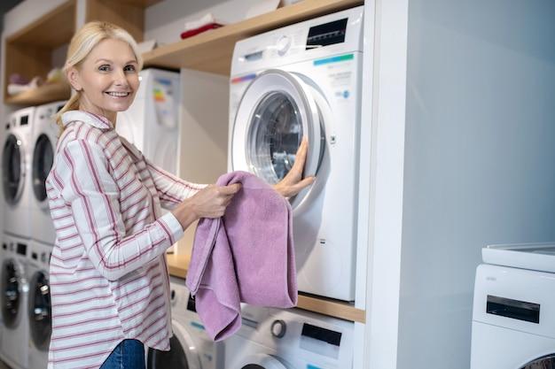 Nowa pralka. blondynka w pasiastej koszuli stojącej w pobliżu pralki