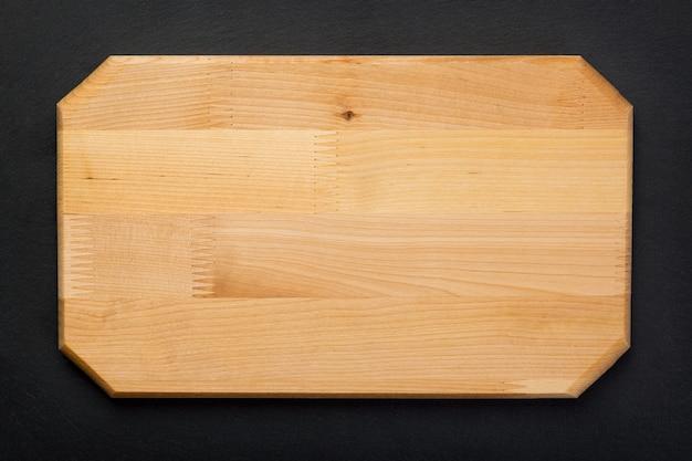 Nowa prostokątna drewniana deska do krojenia na czarnej kamiennej płytce łupkowej. makieta do projektu żywności. widok z góry.