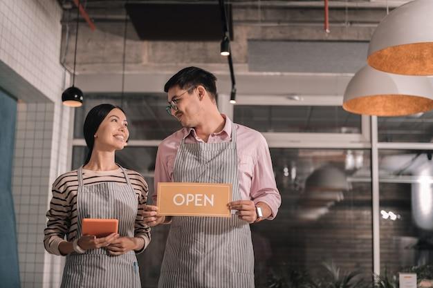 Nowa restauracja. atrakcyjna piękna żona czuje się szczęśliwa otwierając nową restaurację ze swoim mężczyzną