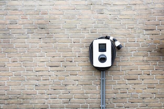 Nowa stacja ładująca do samochodu elektrycznego na ścianie z cegły w domu, słup ładujący z miejscem na kopię,
