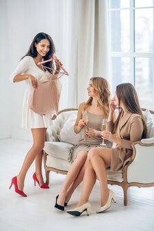 Nowa sukienka. trzy piękne dziewczyny wybierają sukienkę i wyglądają na podekscytowane