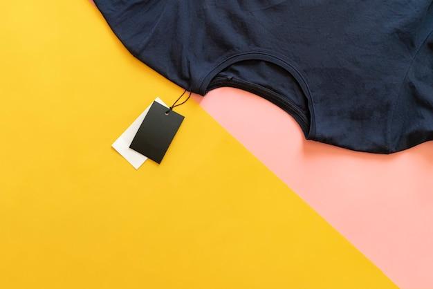 Nowa swobodna koszulka z metką z ceną sprzedaży z miejscem na kopię na różowym i żółtym tle.