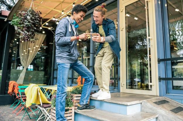 Nowa technologia. radośnie zachwyceni przyjaciele patrzą na siebie podczas sprawdzania nowoczesnego gadżetu