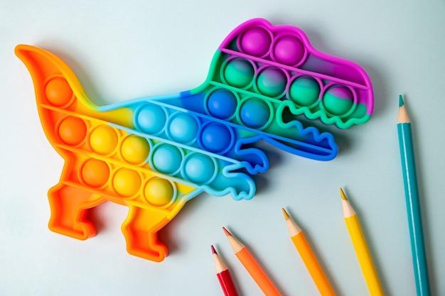 Nowa zabawka silikonowa pop w kształcie dinozaura na niebieskim tlenowa zabawka antystresowa sensoryczna
