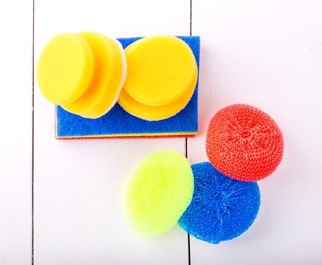 Nowa żółta, czerwona i rozmyta gąbka do mycia naczyń na białym tle ujęcie z góry