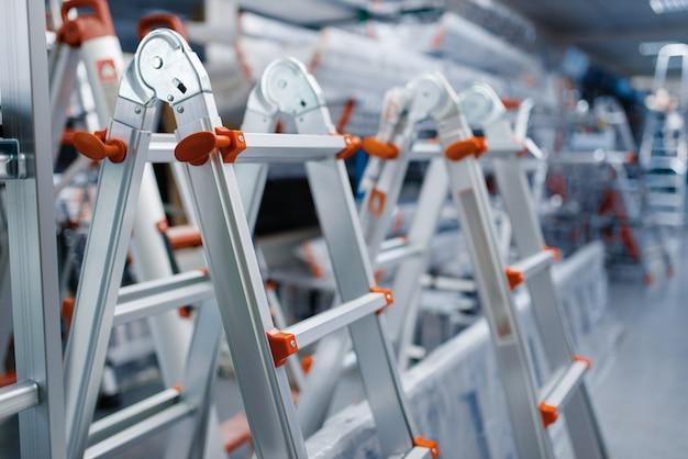 Nowe aluminiowe drabiny w sklepie z narzędziami, nikt. witryna z drabinami, wybór sprzętu w sklepie z narzędziami, supermarket z instrumentami