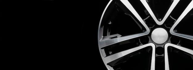 Nowe błyszczące felgi aluminiowe w kolorze czarnym ze srebrnym przodem. ciemne tło.
