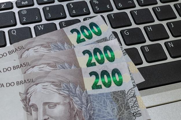 Nowe brazylijskie banknoty na klawiaturze notebooka. dwieście reali.